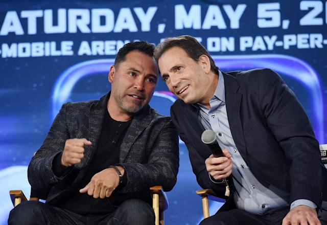 Oscar De La Hoya speaks with Tom Loeffler during a news conference at Microsoft Theater at L.A. Live in Los Angeles. (Getty Images)