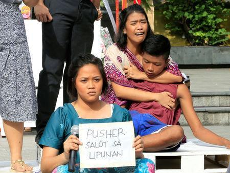 """Filipino theatre artists perform a short musical about the killings under the Philippine government's anti-drug campaign, in Pandacan city, metro Manila, Philippines April 2, 2017. The placard reads, (drug) """"pusher a menace to the society"""". REUTERS/Romeo Ranoco"""
