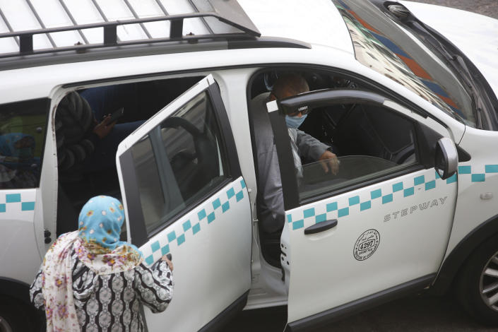 People wear face masks and take a taxi in Casablanca, Morocco, Tuesday, April 6, 2021. Moroccan authorities have announced the discovery of a new local variant of the coronavirus and extended an overnight curfew as infections rise again. (AP Photo/Abdeljalil Bounhar)
