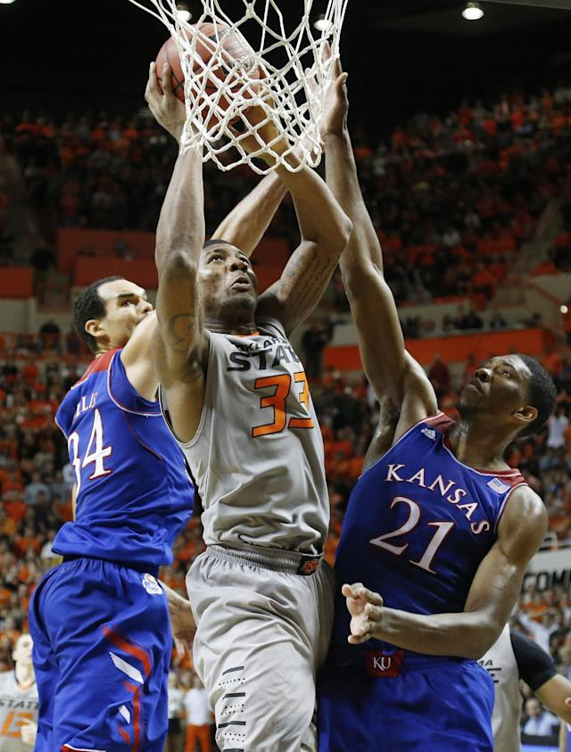 Oklahoma State guard Marcus Smart (33) shoots between Kansas forward Perry Ellis (34) and center Joel Embiid (21) during the second half of an NCAA college basketball game in Stillwater, Okla., Saturday, March 1, 2014. Oklahoma State won 72-65. (AP Photo/Sue Ogrocki)