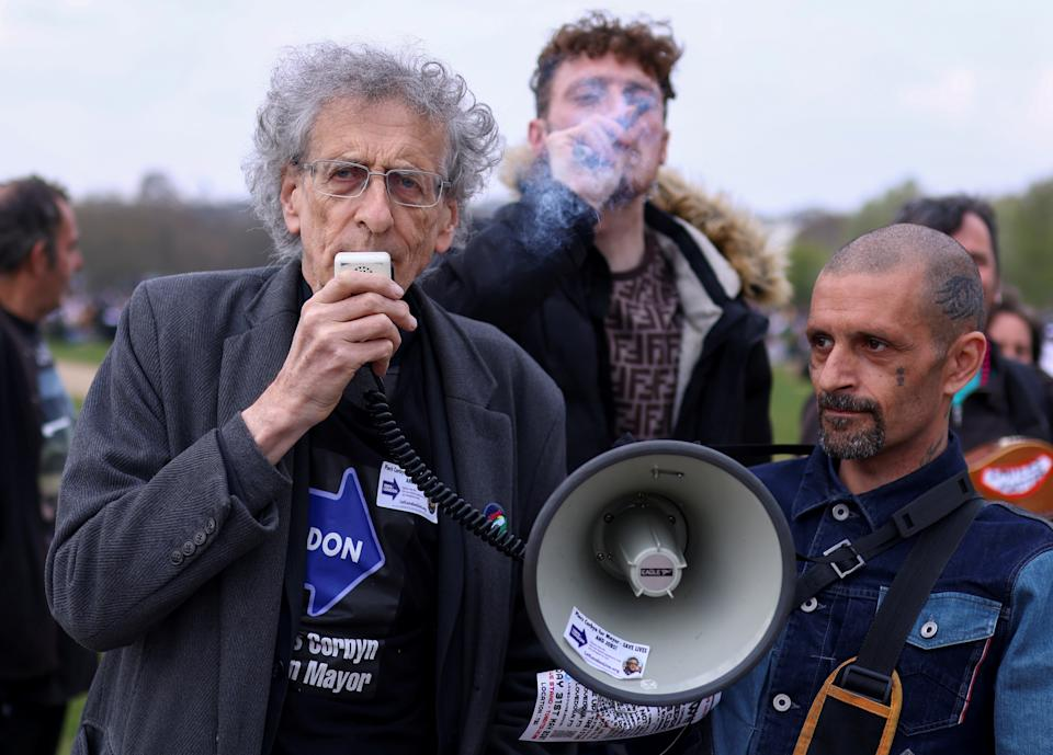 Piers Corbyn, candidate for Mayor of London and brother of former Labour Party leader Jeremy Corbyn, speaks through a megaphone, as a man smokes behind him, during a demonstration in Hyde Park to mark the informal cannabis holiday, 4/20, in London, Britain, April 20, 2021. REUTERS/Tom Nicholson
