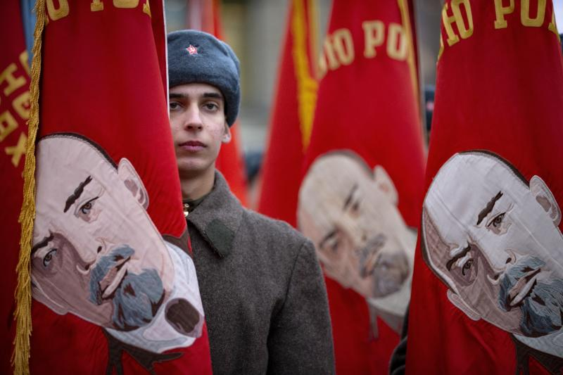 A Russian soldier dressed in Red Army World War II winter uniform stands amid Soviet-era flags as he waits to take part in a reconstruction of a World War II-era parade in Moscow's Red Square, Russia, Thursday, Nov. 7, 2019. The Nov. 7, 1941 parade saw Red Army soldiers move directly to the front line in the Battle of Moscow, becoming a symbol of Soviet valor and tenacity in the face of overwhelming odds. (AP Photo/Alexander Zemlianichenko)