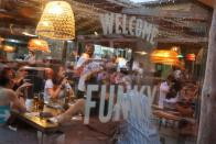 """An employee carrie a pizza for clients, who ordered it through the """"Funky Pay"""" app, at Funky Pizza restaurant, where the app replaces waiters, in Palafrugell"""
