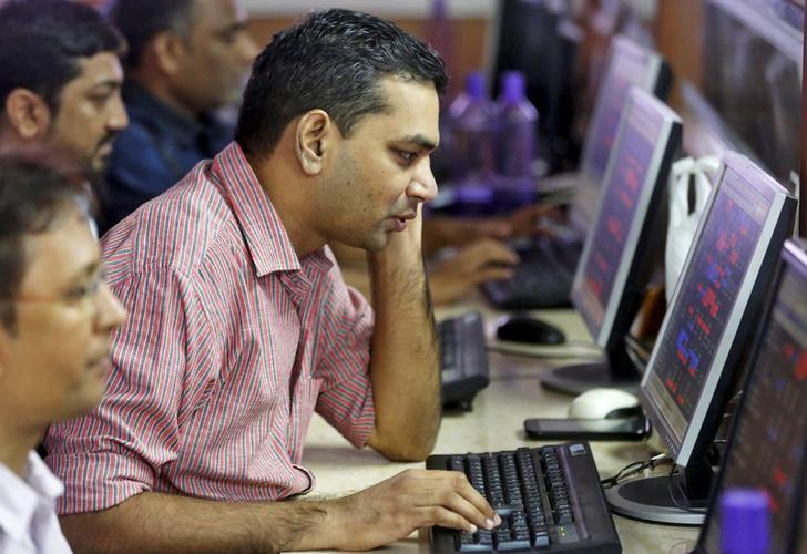 Brokers trade at computer terminals at stock brokerage firm in Mumbai