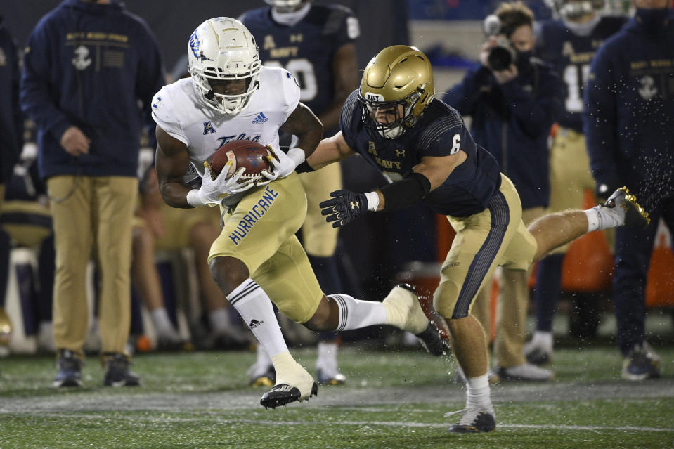 Tulsa wide receiver Keylon Stokes, left, runs with the ball after a catch past Navy defensive back Mitchell West (6) during the second half of an NCAA college football game, Saturday, Dec. 5, 2020, in Annapolis, Md. (AP Photo/Nick Wass)