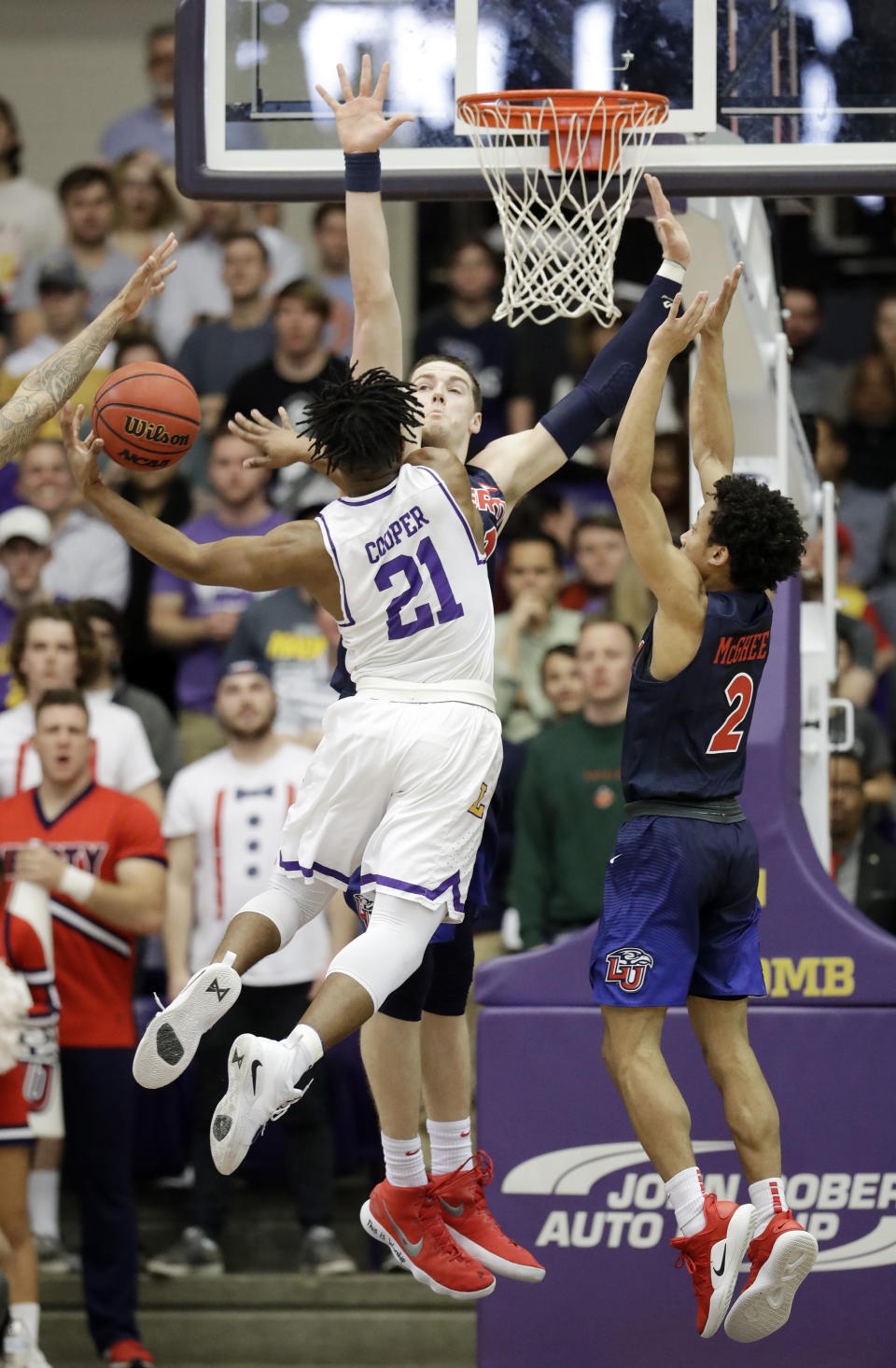 Lipscomb guard Kenny Cooper (21) drives against Liberty forward Scottie James and guard Darius McGhee (2) in the first half of the Atlantic Sun NCAA college basketball tournament championship game Sunday, March 10, 2019, in Nashville, Tenn. (AP Photo/Mark Humphrey)