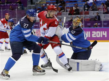 Finland's Petri Kontiola (L) knocks the puck away from Russia's Nikolai Kulyomin and Finland's goalie Tuukka Rask during the first period of their men's quarter-finals ice hockey game at the 2014 Sochi Winter Olympic Games, February 19, 2014. REUTERS/Mark Blinch
