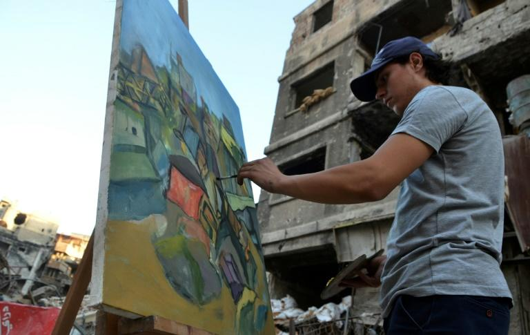An artist paints on a canvas in the Yarmuk Palestinian refugee camp on the southern outskirts of Damascus on August 15, 2018