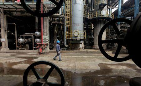 A worker walks past oil pipes at a refinery in Wuhan