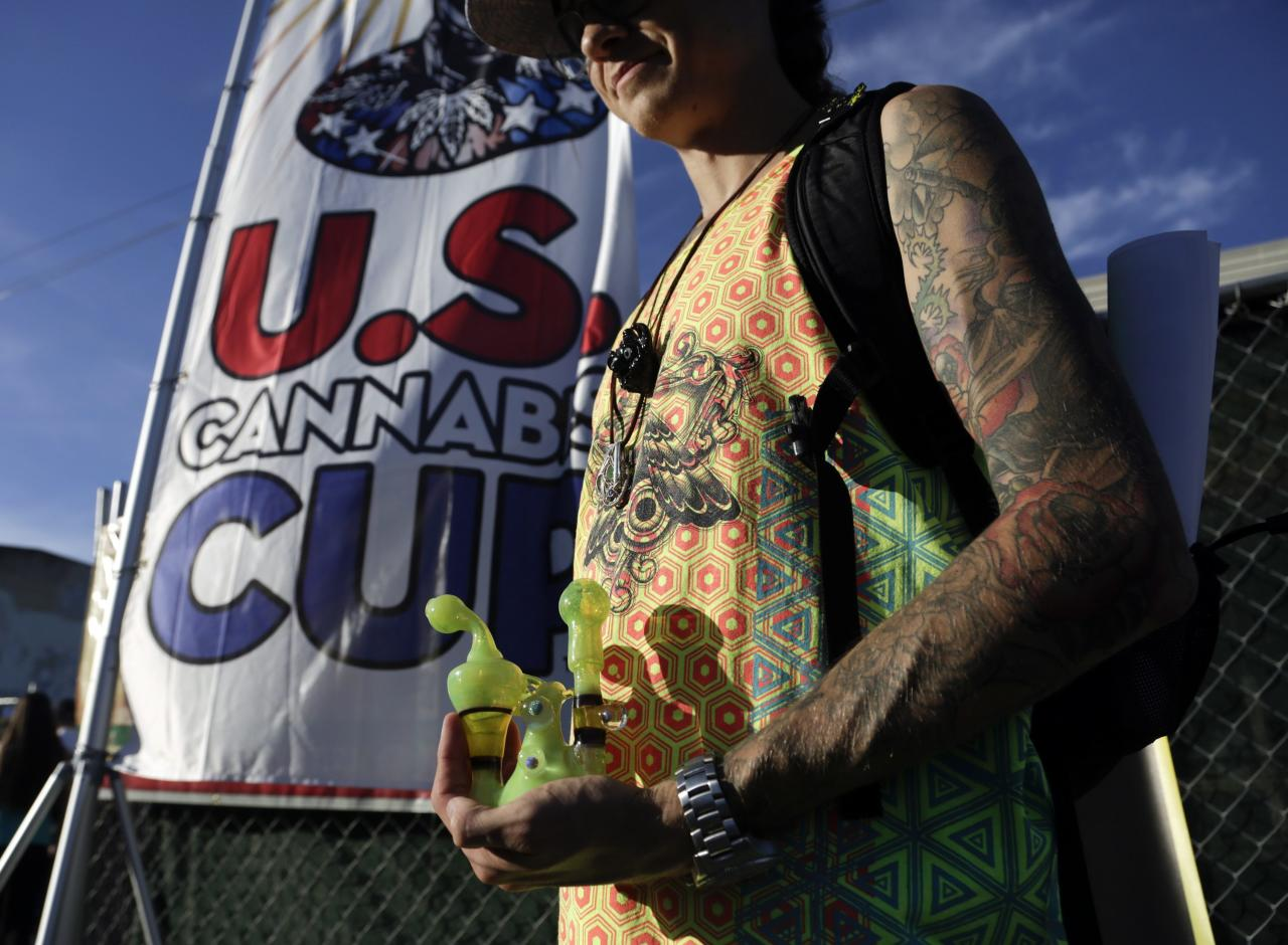 An attendee holds a water pipe at the High Times U.S. Cannabis Cup in Seattle, Washington September 8, 2013. Washington state was one of the first states to legalize marijuana for recreational use after approving separate ballot initiatives last year, even as the drug remains illegal under federal law. The Cup features exhibitions as well as a marijuana growing competition. REUTERS/Jason Redmond (UNITED STATES - Tags: DRUGS SOCIETY)
