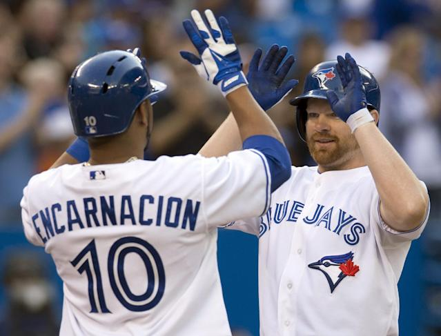Toronto Blue Jays Edwin Encarncacion congratulates teammate Adam Lind on his three-run home run during the first inning of a baseball game against the Colorado Rockies in Toronto on Wednesday, June 19, 2013. (AP Photo/The Canadian Press, Frank Gunn)