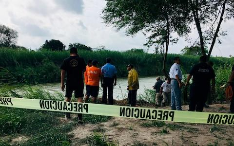 Authorities stand behind yellow warning tape along the Rio Grande bank where the bodies were found