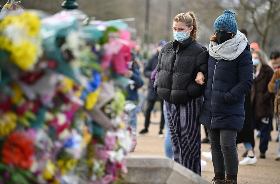 LONDON, ENGLAND - MARCH 13: Members of the public wearing face masks stand before tributes for Sarah Everard at the bandstand on Clapham Common on March 13, 2021 in London, United Kingdom. Vigils are being held across the United Kingdom in memory of Sarah Everard. Yesterday, the Police confirmed that the remains of Ms Everard were found in a woodland area in Ashford, a week after she went missing as she walked home from visiting a friend in Clapham. Metropolitan Police Officer Wayne Couzens has been charged with her kidnap and murder. (Photo by Leon Neal/Getty Images)
