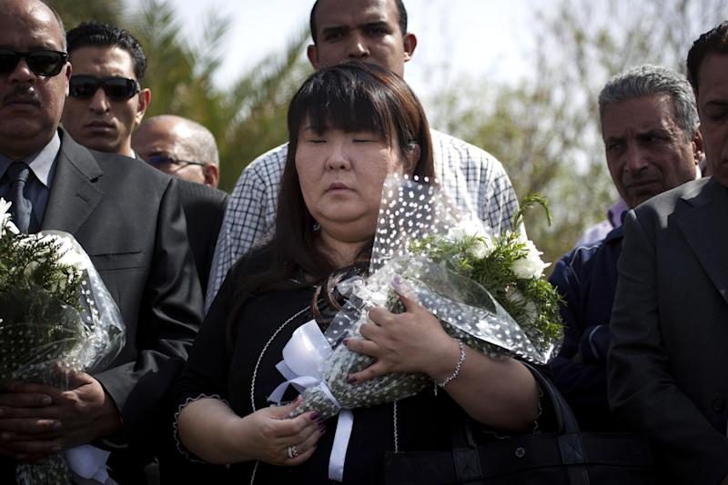 Japanese travel agent Okumura Hatsuko, holds flowers as she pays respect to Japanese tourists that died from a hot air balloon accident, in Luxor, Egypt, Wednesday, Feb. 27, 2013. A hot air balloon carrying tourists over Egypt's ancient city of Luxor caught fire on Tuesday, Feb. 26, 2013 and some passengers trying to escape the flames leaped to their deaths before the craft crashed in a sugar cane field. At least 19 tourists were killed in one of the world's deadliest ballooning accidents. (AP Photo/Nasser Nasser)