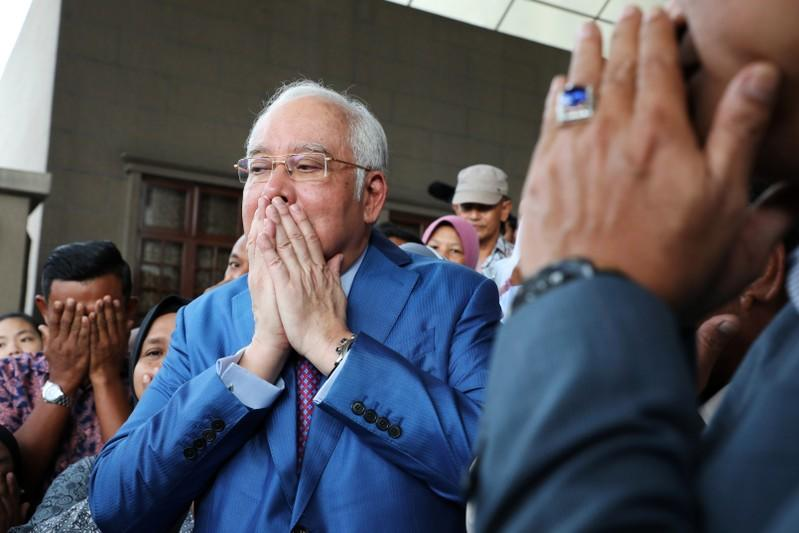 Former Malaysian Prime Minister Najib Razak prays with his supporters before entering a court room at Kuala Lumpur High Court