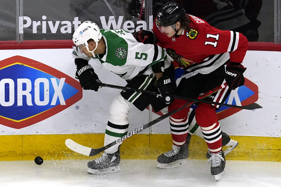 Dallas Stars defenseman Andrej Sekera, left, works for the puck against Chicago Blackhawks center Adam Gaudette during the second period of an NHL hockey game in Chicago, Sunday, May 9, 2021. (AP Photo/Nam Y. Huh)