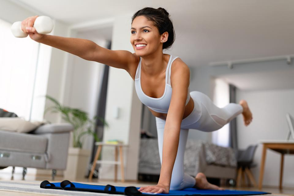Fit beautiful sports woman exercising and training at home
