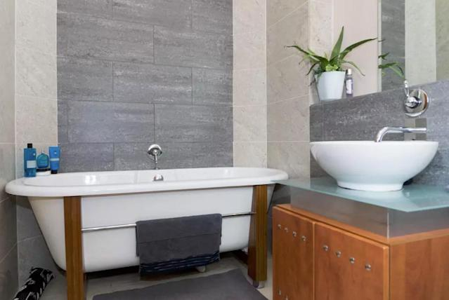 <p>The ultra-modern bathroom features a vessel sink and a soaker tub. </p>