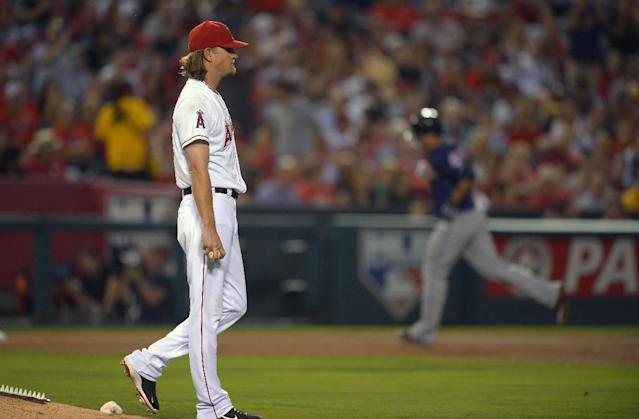 Cleveland Indians' Lonnie Chisenhall, right, rounds third as Los Angeles Angels starting pitcher Jered Weaver looks on after hitting a two-run home run during the fourth inning of their baseball game, Monday, Aug. 19, 2013, in Anaheim, Calif. (AP Photo/Mark J. Terrill)
