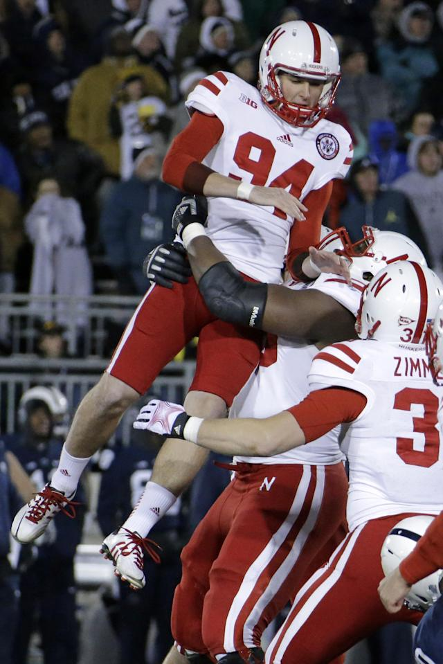 Nebraska kicker Pat Smith (94) leaps is hoisted by teammates after kicking the game-winning field goal in overtime to beat Penn State 23-20 in an NCAA college football game in State College, Pa., Saturday, Nov. 23, 2013. (AP Photo/Gene J. Puskar)
