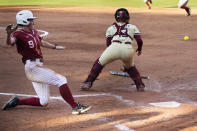 Alabama's Taylor Clark (9) slides safely behind Florida State catcher Anna Shelnutt (13) to score in the third inning of an NCAA Women's College World Series softball game Monday, June 7, 2021, in Oklahoma City. (AP Photo/Sue Ogrocki)