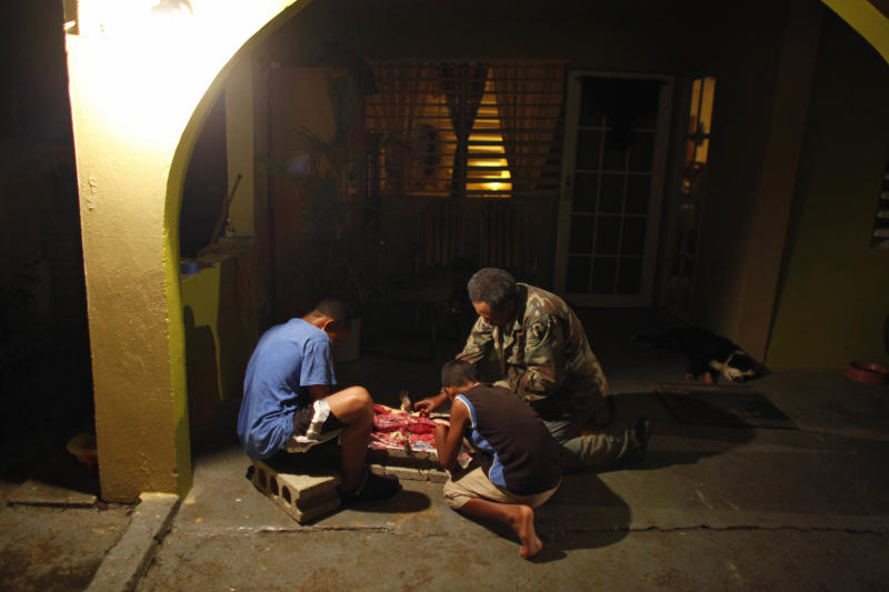 In this Dec. 5, 2012 photo, Daniel Montanez, right, strips the skin of a caiman in his home's driveway with the help of his grandchildren Shalepxis Morales, left, and Shamil Morales in the Los Naranjos neighborhood of Vega Baja, Puerto Rico. A fisherman by trade, Montanez said the caimans first caught his eye during night fishing expeditions. Now, neighbors call him if they have a problem with the reptiles. (AP Photo/Ricardo Arduengo)