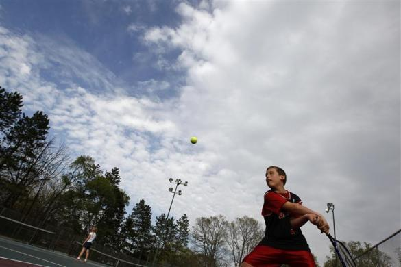 Parker Roos, who suffers from Fragile X, plays tennis at a court near their home in Canton, Illinois, April 4, 2012.