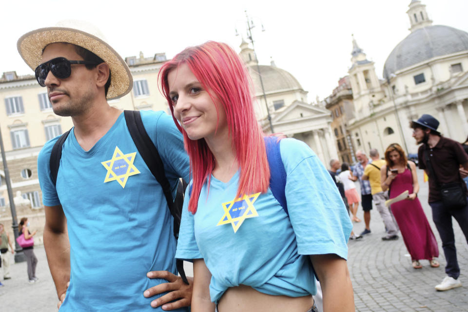 FILE - In this Tuesday, July 27, 2021 filer, people take part in a protest against the COVID-19 vaccination pass in Rome. Protesters in Italy and in France have been wearing yellow Stars of David, like the ones Nazis required Jews to wear to identify themselves during the Holocaust. Some carry signs likening vaccine passes to dictatorships. (Mauro Scrobogna/LaPresse via AP, File)