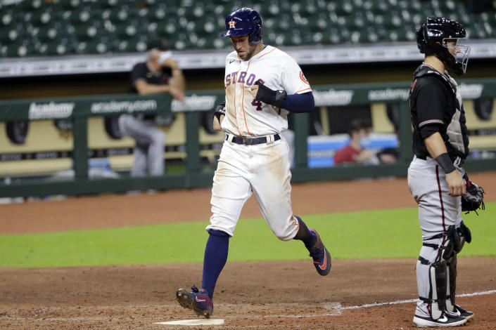 Houston Astros center fielder George Springer, left, scores behind Arizona Diamondbacks catcher Daulton Varsho, right, on the line-drive double by Jose Altuve during the sixth inning of a baseball game Saturday, Sept. 19, 2020, in Houston. (AP Photo/Michael Wyke)