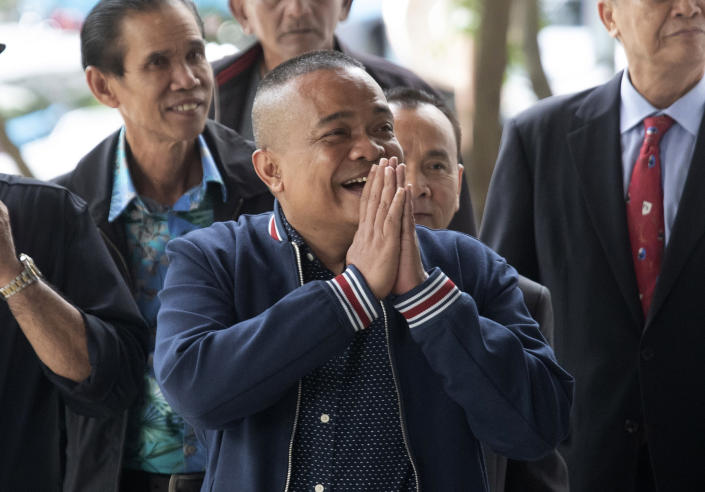 Jatuporn Phromphan, center, one of the leaders of Red Shirt, arrives at the Bangkok Criminal Court in Bangkok, Thailand, Wednesday, Aug. 14, 2019. The court has dismissed charges of terrorism and other offenses against 24 leaders of an extended street protest in 2010 that saw key parts of central Bangkok closed off and random violence that was ended by armed military force. (AP Photo/Sakchai Lalit)