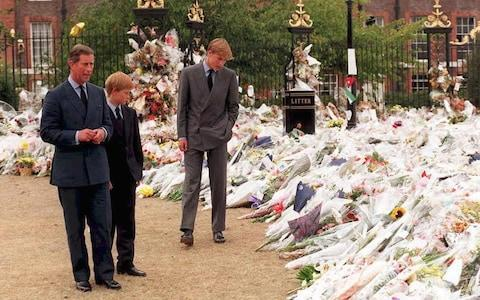 <span>The Prince of Wales and Princes William and Harry inspect thousands of bouquets of floral tributes to their mother Diana, Princess of Wales, outside Kensington Palace on September 5, 1997.</span> <span>Credit: AFP </span>