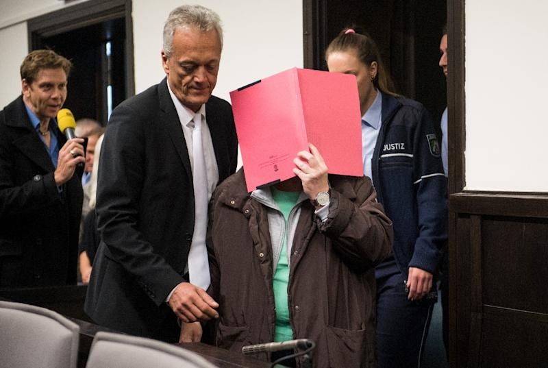 Defendant Angelika Wagener covers herself while arriving in the courtroom of the regional court in Paderborn, western Germany, ahead of her trial on October 26, 2016 (AFP Photo/Bernd Thissen)