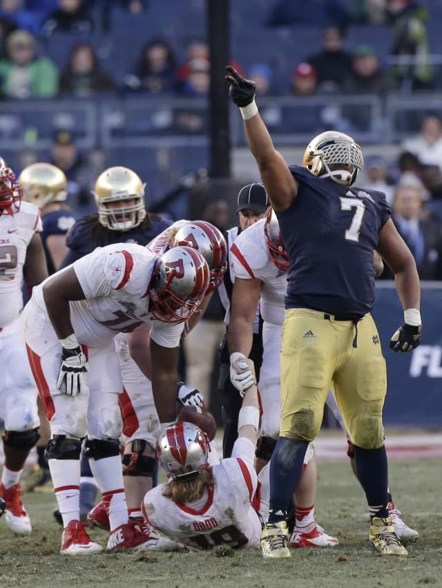 Notre Dame's Stephon Tuitt (7) celebrates a sack on Rutgers's Chas Dodd (19) during the second half of the Pinstripe Bowl NCAA college football game Saturday, Dec. 28, 2013, at Yankee Stadium in New York. Notre Dame won the game 29-16. (AP Photo/Frank Franklin II)