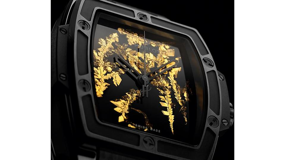 A close up look at the watch's dial with gold crystal detailing and its black ceramic bezel. - Credit: Hublot