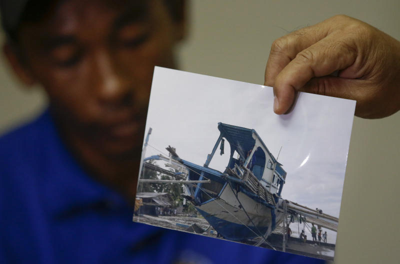 FILE - In this June 17, 2019, file photo, a photo of the damaged Filipino fishing vessel F/B Gimver 1 is shown by one of it's crew Richard Blaza, left, during a press conference by Department of Agriculture Secretary Emmanuel Pinol in metropolitan Manila, Philippines. The Philippines' top diplomat says he has filed a diplomatic protest after an anchored fishing boat was hit by a suspected Chinese vessel which then abandoned the 22 Filipino fishermen as the boat sank in the disputed South China Sea. (AP Photo/Aaron Favila, File)