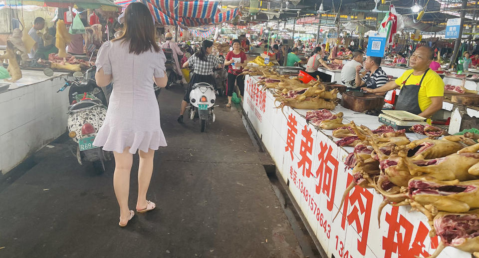 A woman walks through a market with dog carcasses on display.