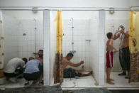 Wrestlers try to recover on the shower room after they competed on the last day of the 660th instalment of the annual Historic Kirkpinar Oil Wrestling championship, in Edirne, northwestern Turkey, Sunday, July 11, 2021.Thousands of Turkish wrestling fans flocked to the country's Greek border province to watch the championship of the sport that dates to the 14th century, after last year's contest was cancelled due to the coronavirus pandemic. The festival, one of the world's oldest wrestling events, was listed as an intangible cultural heritage event by UNESCO in 2010. (AP Photo/Emrah Gurel)