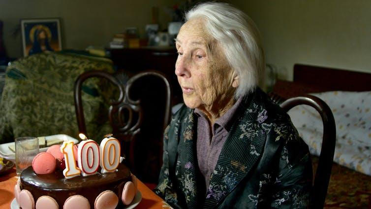 A 100-year-old woman blows out the candles on her birthday cake.