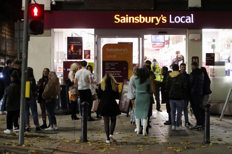 People wait outside a Sainsbury's the night before a local lockdown amidst the spread of the coronavirus disease (COVID-19) in Manchester