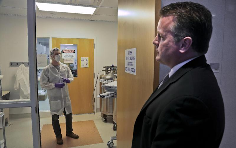 In this April 15, 2014 photo, Mark Desire, right, assistant director for forensic biology at the Office of Chief Medical Examiner, talks with forensic criminalist Michael Mosco as he prepares to enter the bone grinding room at the Office of Chief Medical Examiner in New York. The room is central to the examination of bone DNA from those who died on Sept. 11, 2001. Forensic scientists are still trying to match the bone with DNA from victims who have never been identified. (AP Photo/Bebeto Matthews)