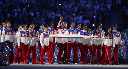 Russia's athletes carry their national flag in the closing ceremony for the Sochi 2014 Winter Olympic Games February 23, 2014. REUTERS/Lucy Nicholson