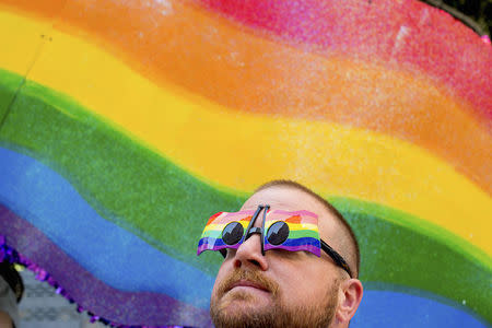 John Lucas stands in front of a rainbow flag at the San Francisco Gay Pride Festival in California