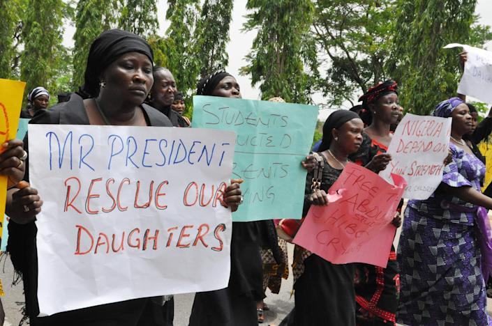 """Unidentified mothers call for the president to help, during a demonstration with others who have daughters among the kidnapped school girls of government secondary school Chibok, Tuesday April 29, 2014, in Abuja, Nigeria. Two weeks after Islamic extremists stormed a remote boarding school in northeast Nigeria, more than 200 girls and young women remain missing despite a """"hot pursuit"""" by security forces and desperate parents heading into a dangerous forest in search of their daughters. Some dozens have managed to escape their captors, jumping from the back of an open truck or escaping into the bush from a forest hideout, although the exact number of escapees is unclear. (AP Photo/ Gbemiga Olamikan)"""