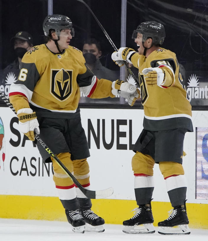 Vegas Golden Knights' Mattias Janmark, left, celebrates after Jonathan Marchessault, right, scored against the San Jose Sharks during the third period of an NHL hockey game Wednesday, April 21, 2021, in Las Vegas. (AP Photo/John Locher)