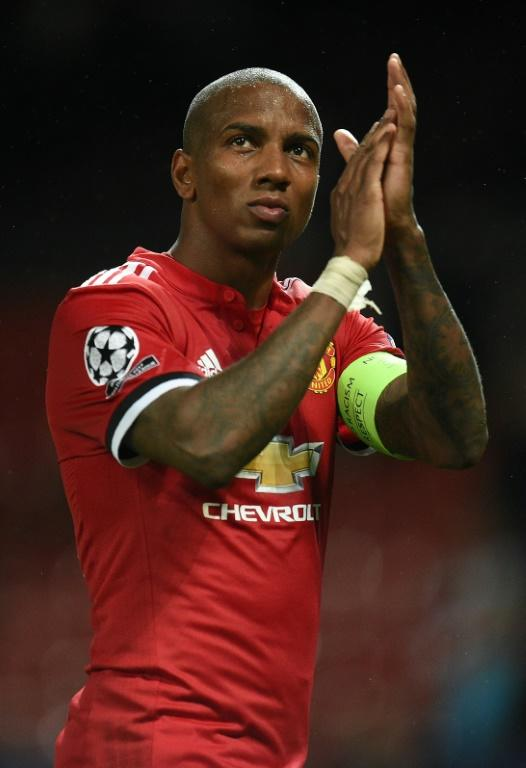 (FILES) In this file photo taken on September 12, 2017 Manchester United's English midfielder Ashley Young applauds the fans following the UEFA Champions League Group A football match between Manchester United and Basel at Old Trafford in Manchester, north west England on September 12, 2017.Manchester United triggered a one-year contract extension clause on March 19, 2018 to retain the services of Ashley Young until 2019. The 32-year-old's deal was due to expire this summer, but United have confirmed they have taken up the option of an extra 12 months