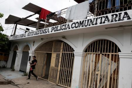 A vigilante is pictured leaving the command headquarters in the municipality of Coahuayana