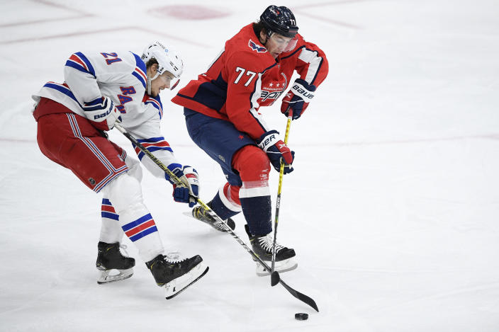 Washington Capitals right wing T.J. Oshie (77) and New York Rangers center Brett Howden (21) battle for the puck during the second period of an NHL hockey game, Saturday, Feb. 20, 2021, in Washington. (AP Photo/Nick Wass)