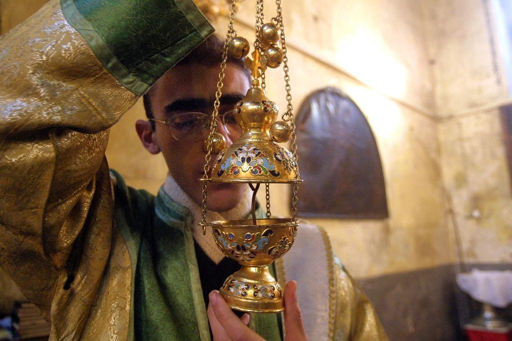 BETHLEHEM, WEST BANK:  An Armenian priest prepares an incense burner for the noon service in the Church of the Nativity in Bethlehem, the biblical birthplace of Jesus Christ. File photo: 2003