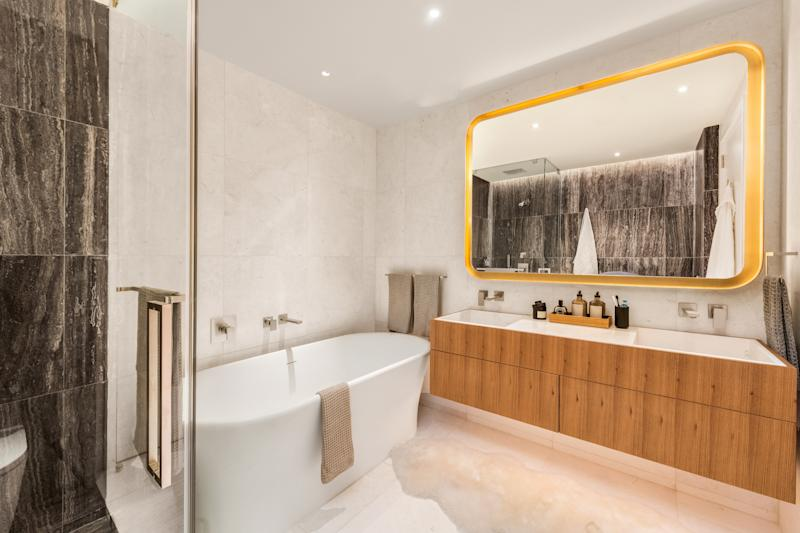 The master bathroom features an oak vanity and a brown travertine shower (at left). Cream-colored marble wraps the walls and floor.