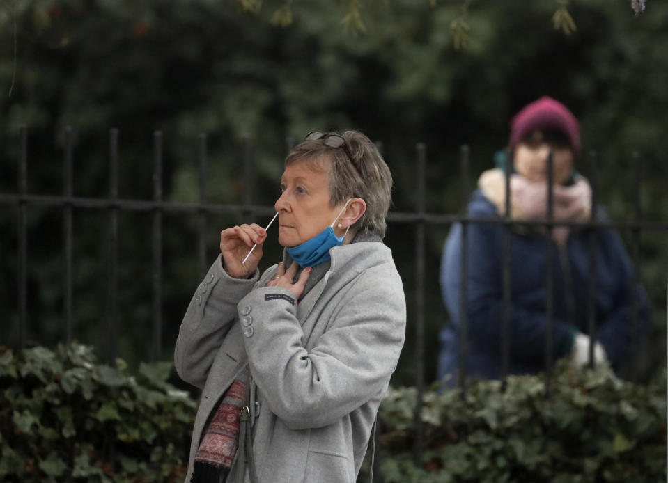 A woman takes her own COVID-19 test at a newly set-up testing facility in a car park in West Ealing, London, Tuesday, Feb. 2, 2021, after it emerged that the South African strain of the coronavirus may have started spreading in the local community. (AP Photo/Frank Augstein)